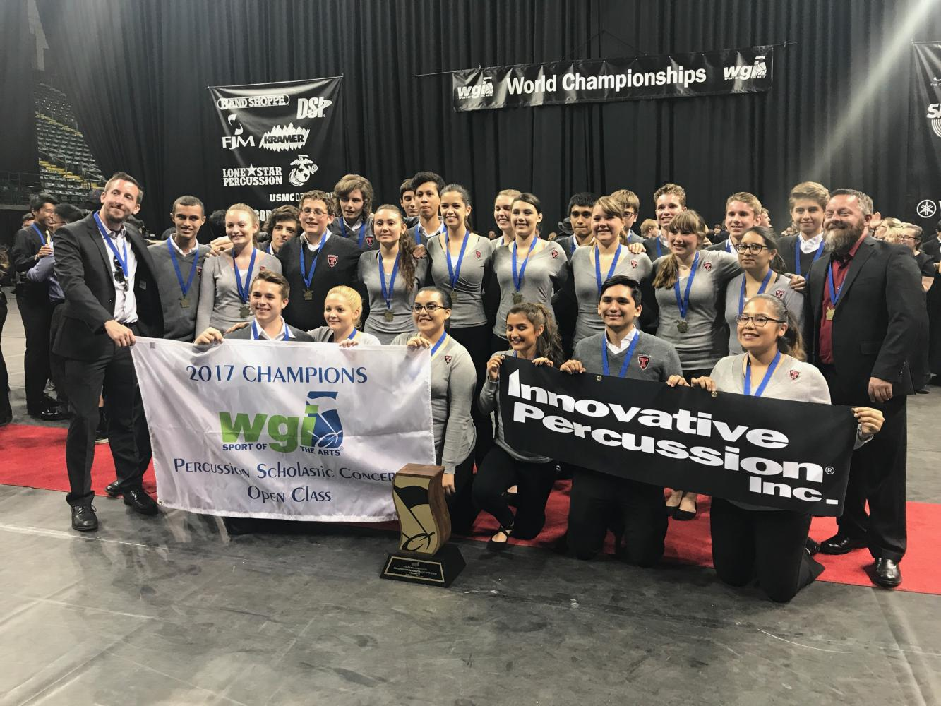 The Winter Percussion Group Accepting/ Taking a picture of there accomplishment of receiving 1st place at an International Competition.