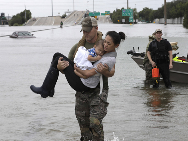 Houston Police officer Daryl Hudeck carries Catherine Pham and her 13-month-old son, Aiden, after rescuing them from their home surrounded by floodwaters on Sunday in Houston.
