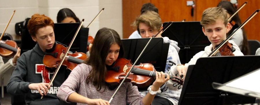 Orchestra students practicing their instruments