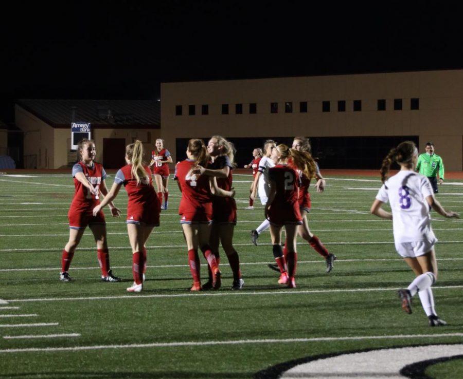 The Girls Varsity soccer team celebrates when a goal is scored.