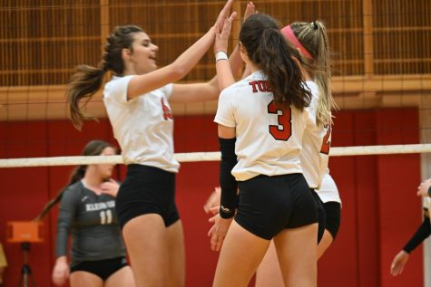 The varsity volleyball team celebrates after scoring a point against Klein Oak.